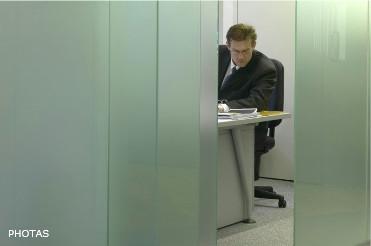Сотрудник офиса в своем кабинете во время рабочего дня. Бизнес, страхование, банк, мужчина, стекло, перегородка.