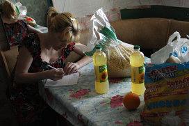 """Светлана Кудрявцева заполняет расписку в получении продуктов от фонда """"Возрождение"""""""